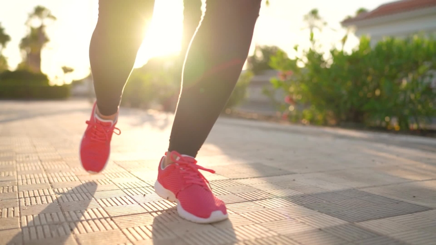 Close up of legs of a woman running along the palm avenue at sunset #1033383572