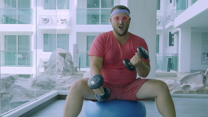 Playful fat man in a pink T-shirt and pink glasses is engaged in fitness with dumbbells and a fit ball in the gym.  | Shutterstock HD Video #1033418882