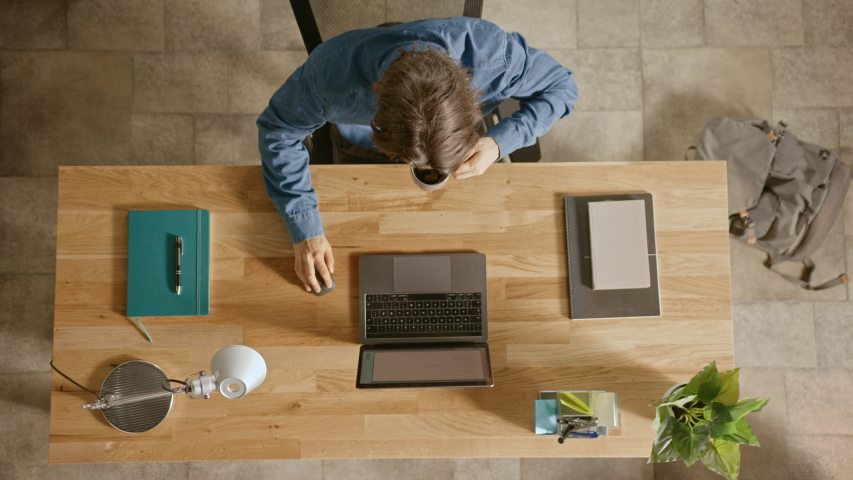 Top View Zoom Out Shot: In the Office Businessman Sitting at the Wooden Desk Opens Laptop and Starts Working He Drinks Coffee, Types, Writes Emails, Surfs the Internet, Designs Software | Shutterstock HD Video #1033427462