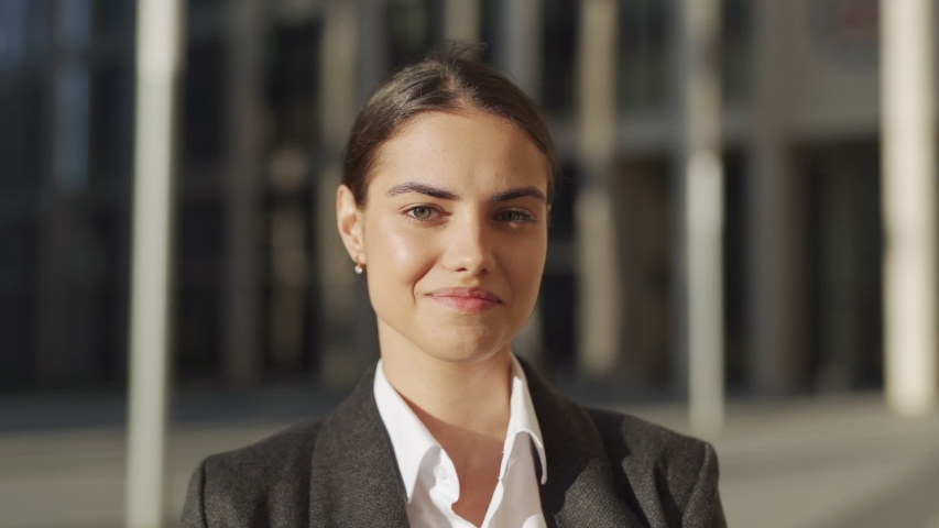 Head and shoulders slow motion portrait of beautiful and confident young woman in formal suit standing outdoors, looking at camera and smiling  | Shutterstock HD Video #1033442102