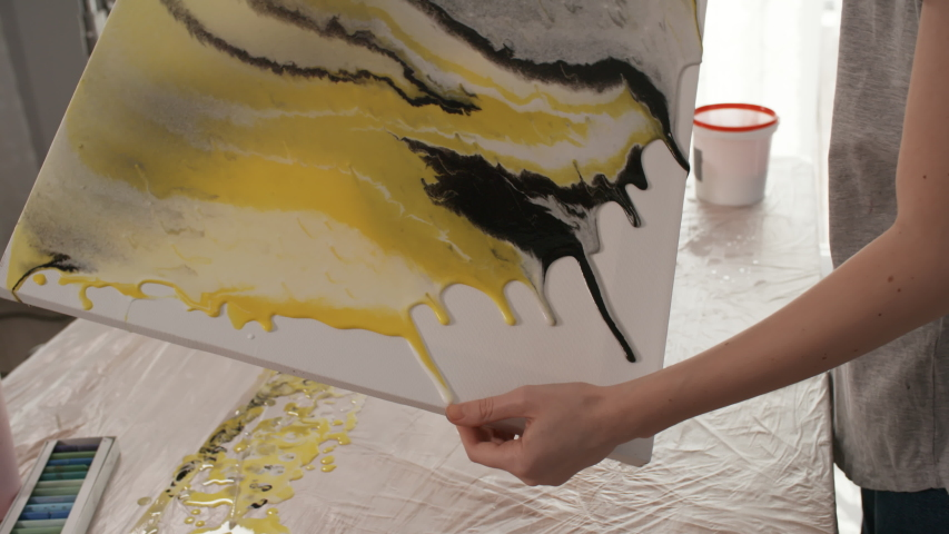 Handheld camera shot of professional female painter tilting canvas with acrylic paints flowing over edges while making fluid painting in art studio   Shutterstock HD Video #1033458152