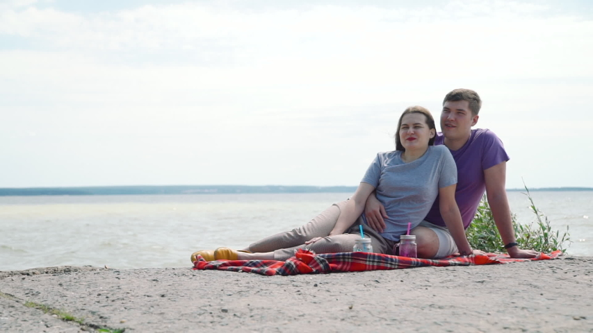 Man and Woman Hugging and Talking While Sitting on the Plaid. Young Couple Having Picnic near the Sea in Windy Summer Day. Slow Motion. Lifestyle, Love, Dating, Vacation Concept | Shutterstock HD Video #1033644242