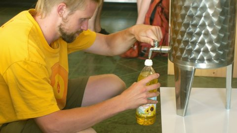 PRAGUE, CZECH REPUBLIC, MAY 25, 2019: Sunflower oil organic quality bio, steel barrel or bowl, for cold food and fried foodstuff, the man pours gold oil in the store shop