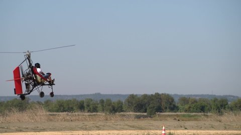 Ultralight gyrocopter autogyro with pilot flying low above the ground on high speed