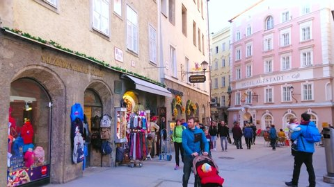 SALZBURG, AUSTRIA - FEBRUARY 27, 2019: The narrow shopping street of Altstadt (old town) with many small stores, offering sport stuff, clothes, souvenirs and local foods, on February 27 in Salzburg