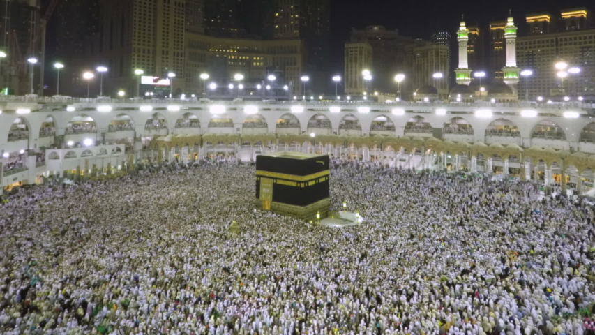 Time lapse video of Muslim pilgrims circling around the holy Kaaba at night during Hajj inside al Masjid al Haram in Mecca, Saudi Arabia. Camera zooms out from the Kaaba.