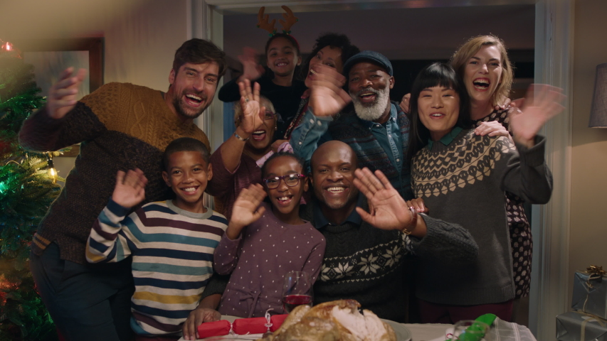 african american family posing for photo with friends at christmas dinner party waving enjoying festive holiday reunion celebrating at home 4k
