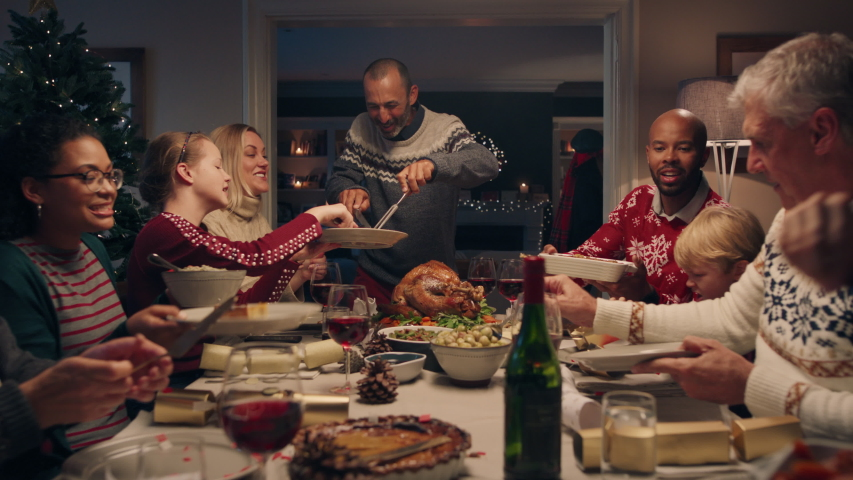 Family christmas dinner man cutting turkey serving delicious meal at festive celebration people sitting at table enjoying delicious feast celebrating holiday at home 4k footage | Shutterstock HD Video #1033939982
