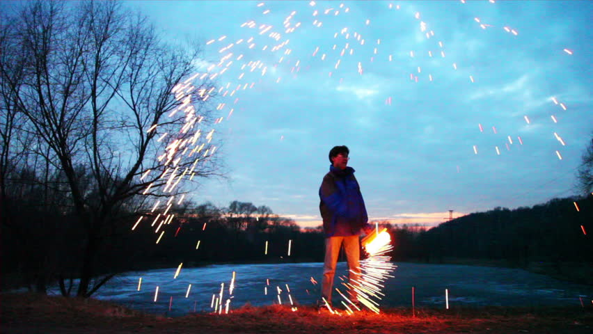 man stands at night in winter woods and rotates hand with shone bengal fire, around scatter fountain of spark