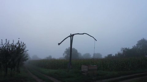 Still timelapse of a shadoof in the foggy sunrise. Some people are walking on the village path.