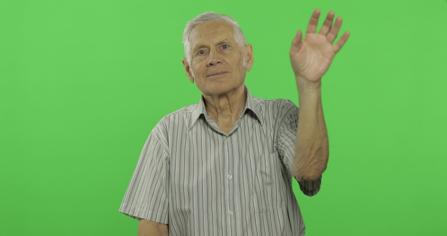 Senior man waving with hands to camera. Handsome old man on chroma key background. Positive elderly grandfather in grey shirt. Place for your logo or text. Chroma key. Green screen background | Shutterstock HD Video #1034085692