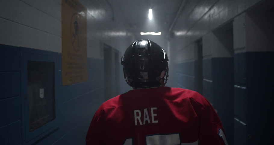 Dramatic moment as hockey player walks down hockey arena hallway walking towards the rink during the playoffs. #1034197022