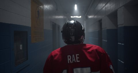 Dramatic moment as hockey player walks down hockey arena hallway walking towards the rink during the playoffs.