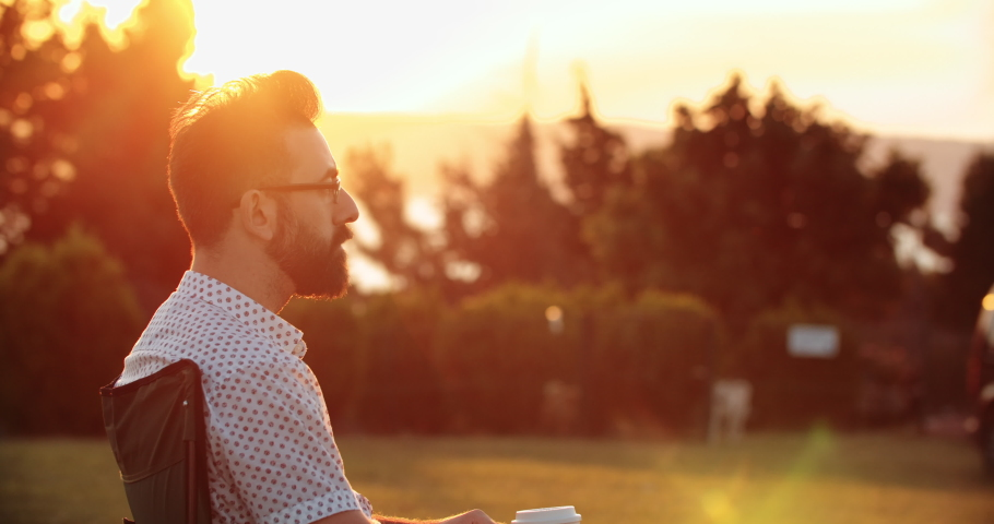 Handsome man drinking coffee in public park at sunset closeup | Shutterstock HD Video #1034197772