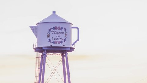 LINDSTROM, MN - MARCH 2018 - A Telephoto Close Up Timelapse Shot of the Rural Minnesota Icon Teapot Water Tower against a Dramatic Sunset Sky 4K UHD