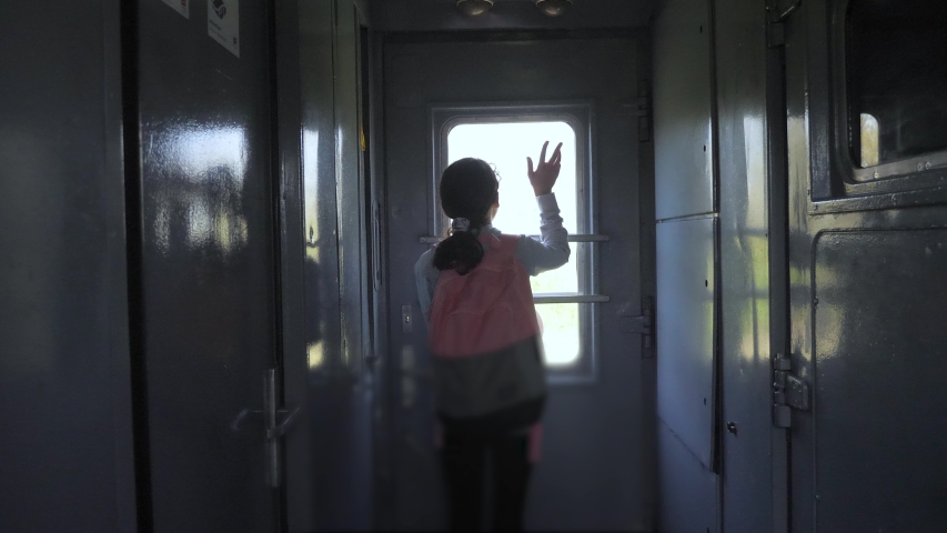 Little teenage girl is a backpacker traveling by train. lifestyle travel transportation railroad concept. tourist school girl in the train wagon with backpack looking out the window waving his hand | Shutterstock HD Video #1034334872