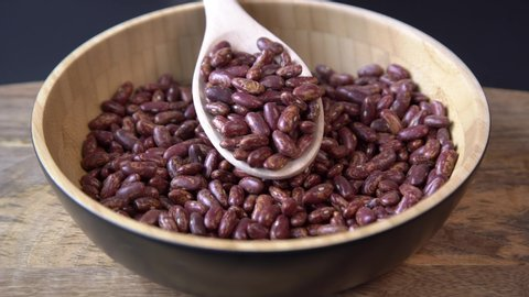 Red beans falling into a wooden bowl. Wooden background. Closeup. Food video. Uncooked beans Raw cereal falling into beautiful dishes Macro