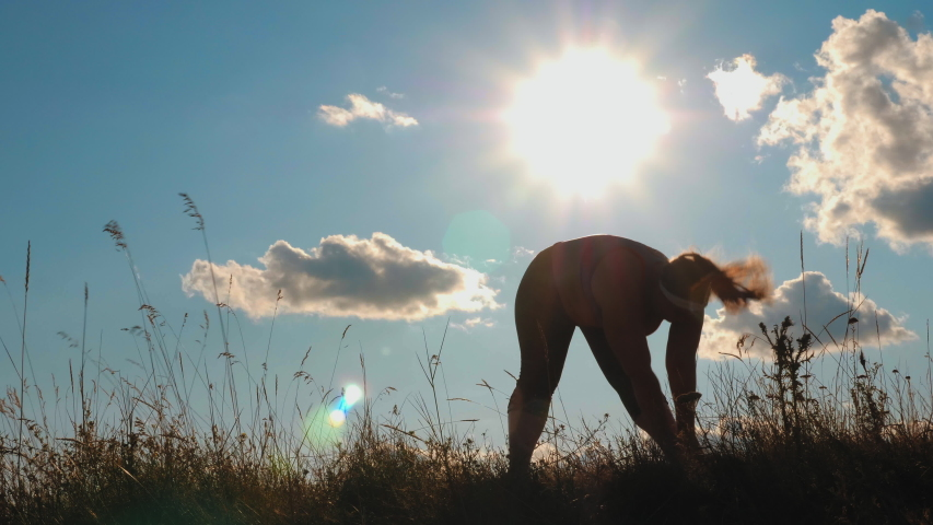 Silhouette: Young plus size girl doing sport exercises on grass spending time in highlands in the morning. Slow-motion video