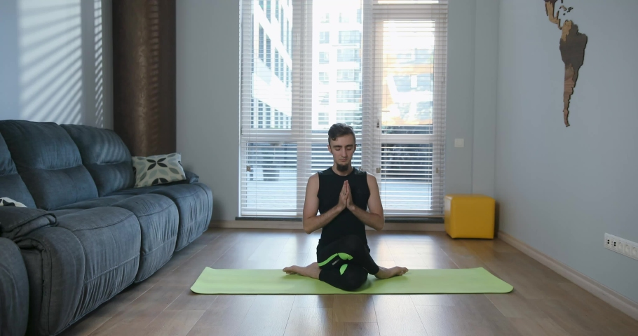 Indoor shot of handsome young man in sportwear practicing yoga on a mat in living room at home. Cozy spacious room and pleasant atmosphere. 4K video | Shutterstock HD Video #1034382722
