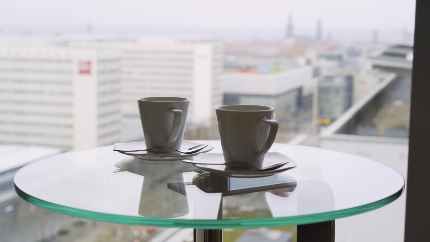 Two cup tea or coffee on table against big window. Motion shot side view mugs on glass with reflection in luxury hotel suite with view above city and hand taking one. Concept summer vacation  | Shutterstock HD Video #1034418662