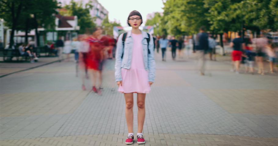 Time lapse of attractive teenage girl standing in city center in busy street looking at camera wearing trendy clothes while crowds of people are walking by. #1034434682