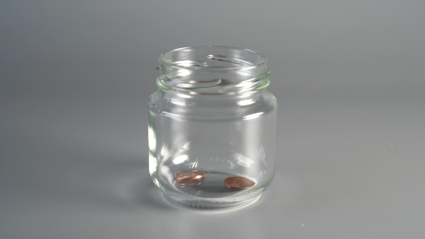 Coins cents falling into a glass jar | Shutterstock HD Video #1034458862