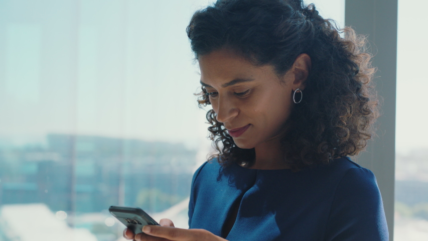 Independent business woman using smartphone texting female executive checking emails browsing messages on mobile phone in office | Shutterstock HD Video #1034474642