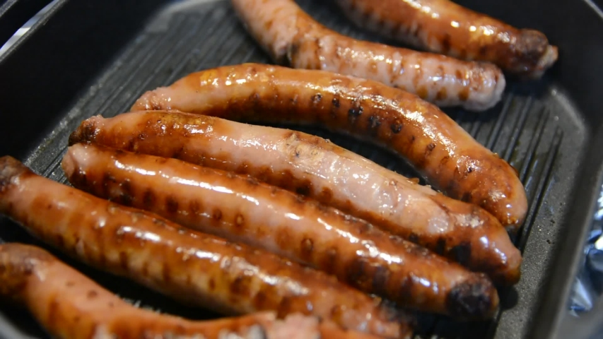 Delicious grilled pork sausages rollin on hot grill pan   Shutterstock HD Video #1034475032