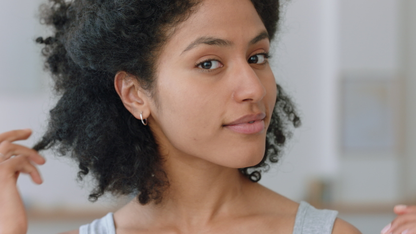 Portrait beautiful mixed race woman looking in mirror fixing hair getting ready at home enjoying natural beauty 4k | Shutterstock HD Video #1034504822