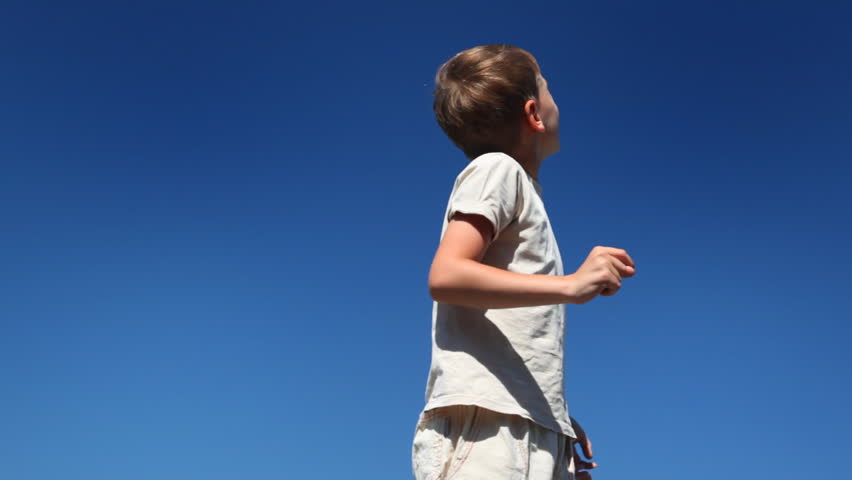 boy turns, says and looks showing his hand up against blue sky in clear sunny day