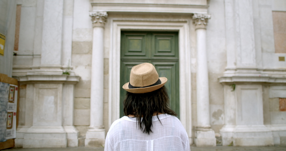 Bird flying by as traveller stands in front of massive antique door from behind in fedora in historic Venice Italy | Shutterstock HD Video #1034515292
