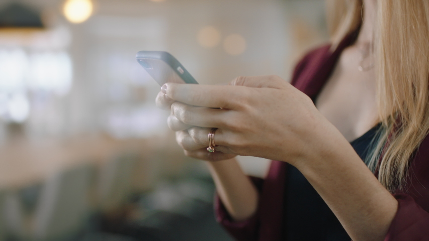 Beautiful blonde business woman using smartphone in office texting sending emails planning meetings networking online browsing messages on mobile phone technology 4k | Shutterstock HD Video #1034544392