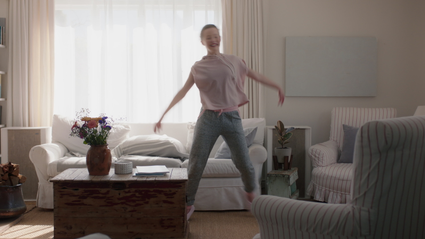 Happy teenage girl dancing at home having fun celebrating weekend with funny dance moves playful teen enjoying freedom 4k footage | Shutterstock HD Video #1034555102
