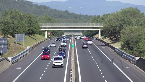 Motorway in Tuscany, August 2019, Regular traffic on Sunday morning with cars traveling in both north and south directions for the summer exodus vacations. Trucks don't travel, just cars and buses