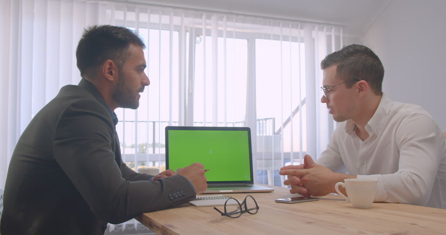 Portrait of two adult successful businessmen having a formal discussion with laptop with green chroma screen in the office indoors workplace | Shutterstock HD Video #1034636342