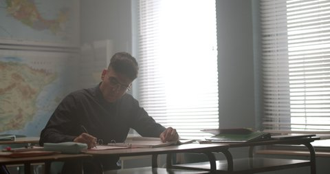 Young student studying in class, reading and writing in notebook