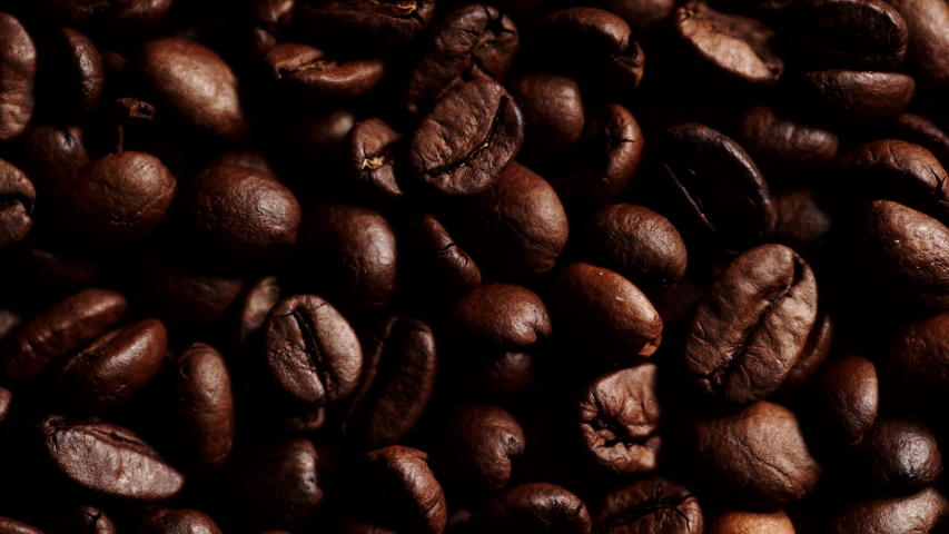 Roasted brown coffee beans as background. Close up. Delicate lighten up effect | Shutterstock HD Video #1034665472