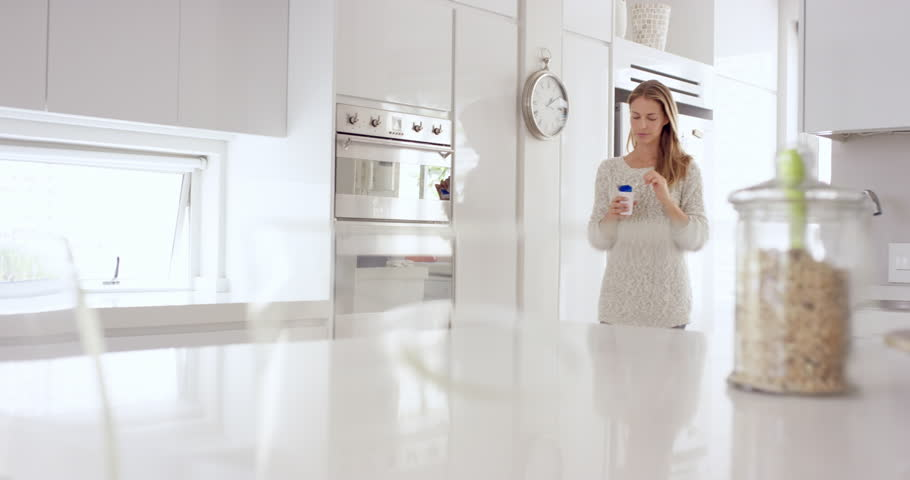 Woman eating natural yogurt in kitchen of white clean luxury home