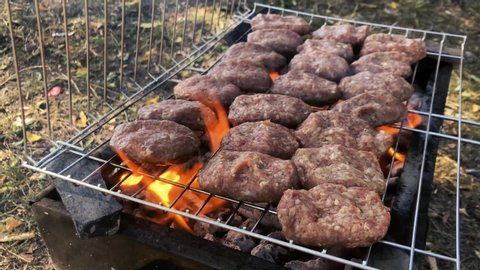 meatballs cooked in a flaming barbecue and wire grill
