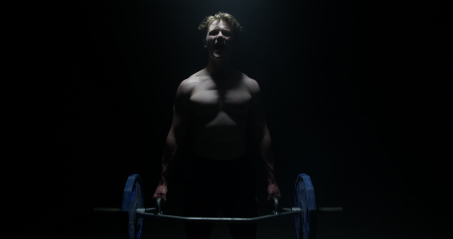 Shot Of Strong Shirtless Male Weightlifter Looking At The Camera And Lifting Weights In A Dark Background | Shutterstock HD Video #1034803982