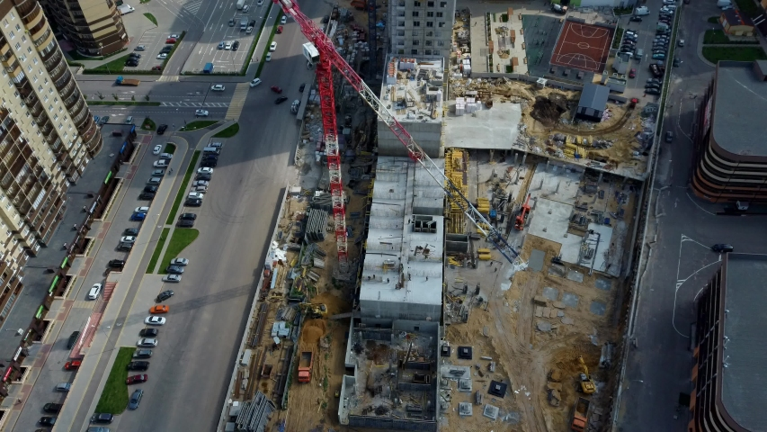 Aerial view of the construction site and construction equipment. The concept of urban infrastructure and construction. | Shutterstock HD Video #1034820962