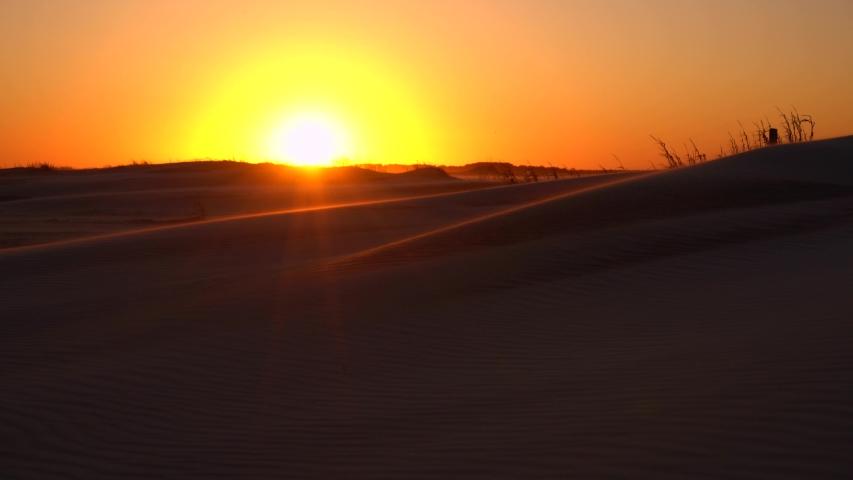 Sand dune forming on a barren, sandy, coastal shoreline during sunset | Shutterstock HD Video #1034834822
