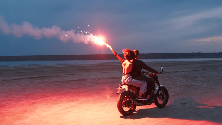 Couple riding on vintage motorcycle with red burning signal fire after sunset on beach, slow motion | Shutterstock HD Video #1034862872