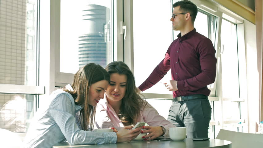 Businesswomen using cellphone and smiling to the camera in the office  | Shutterstock HD Video #10348682