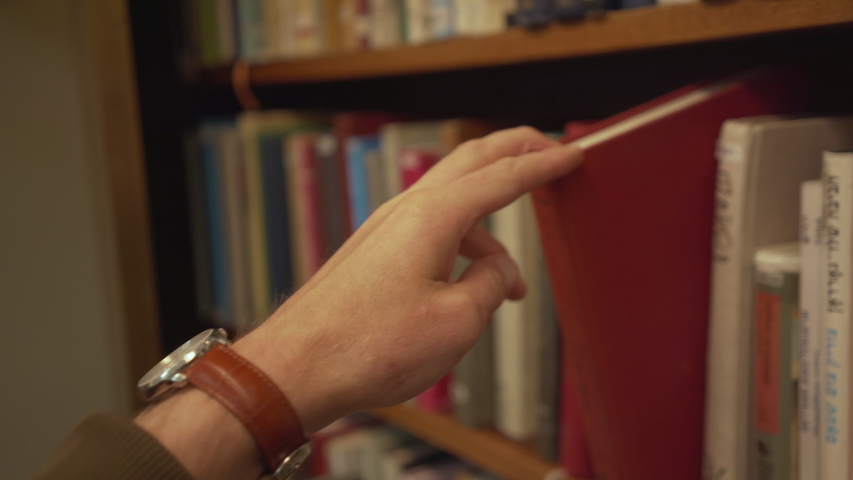 Hand reaches for and pulls books from bookshelf | Shutterstock HD Video #1034874362