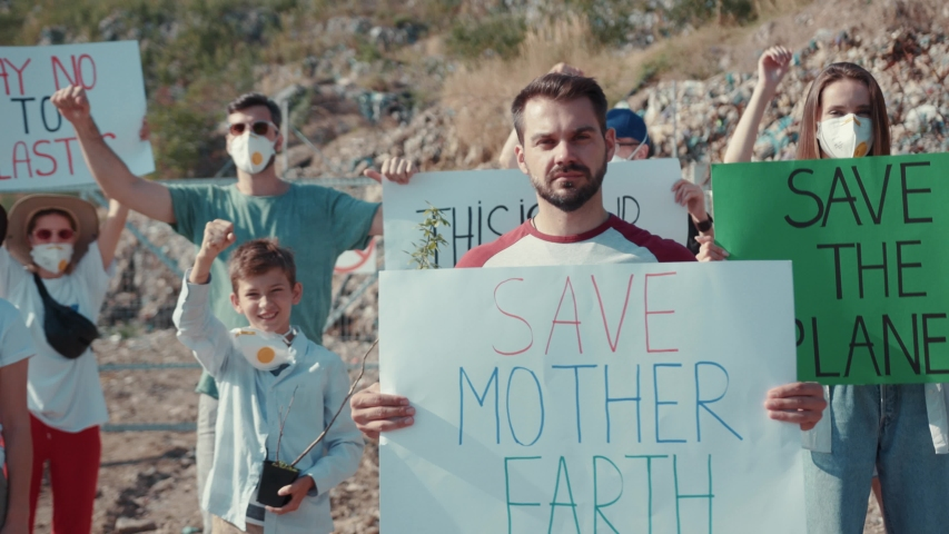 Portrait of male activist with Save Mother Earth poster protesting with friends at a landfill site. Volunteers movement against earth pollution. #1034925842