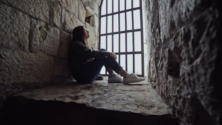 Girl sits in a fortress behind bars and she grieves | Shutterstock HD Video #1034994962