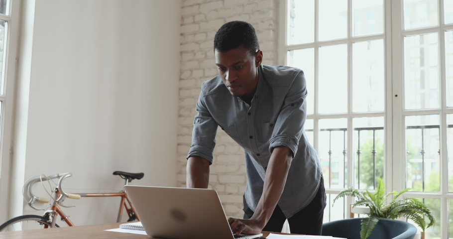Serious smiling young african american businessman working on laptop standing at office desk, male executive professional entrepreneur using computer corporate software doing paperwork at workplace | Shutterstock HD Video #1035023852