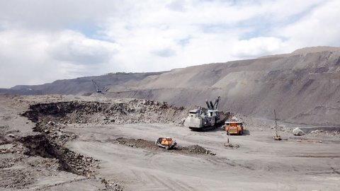 A powerful excavator loads mining trucks. Excavation and loading of rock mass into transport. Timelapse