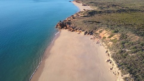 Scenic panoramic aerial drone view of flight high above ocean and remote beach in Western Australia, with rocky cliff coastline, summer sunny blue sky and horizon as background and copy space.